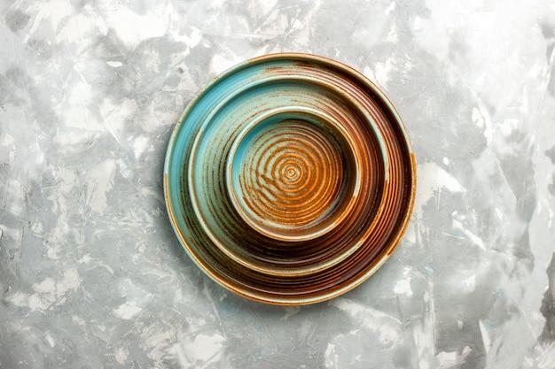 Vue de dessus des plaques brunes rondes de différentes tailles vides isolés sur la surface gris clair