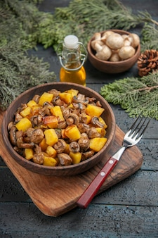 Vue de dessus plat et branches bol en bois de pommes de terre et de champignons sur la planche à découper à côté de la fourchette sous une bouteille d'huile bol de champignons blancs et branches d'épinette avec cônes
