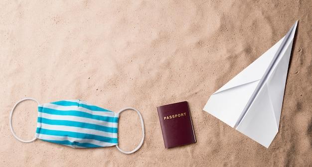 Vue de dessus à plat du masque facial, du passeport et de l'avion en papier, des vacances d'été et du concept de voyage.