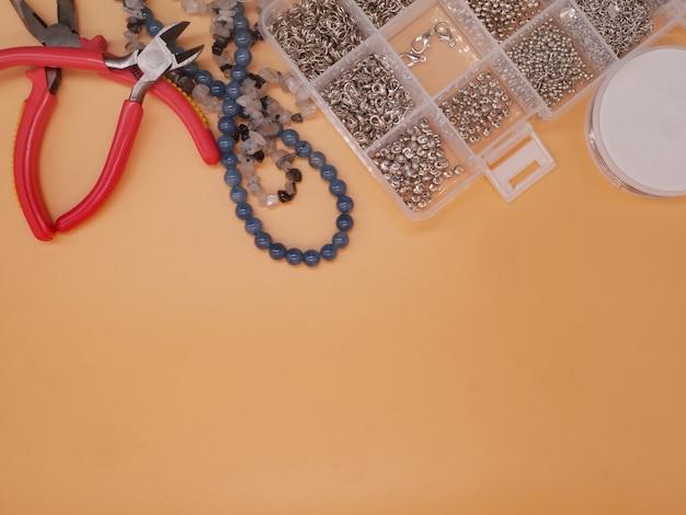 Vue de dessus plat, fournitures de perles sur fond orange