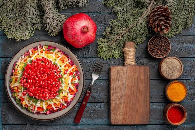 Vue de dessus plat de grenade de pommes de terre graines de grenade dans l'assiette à côté de la fourchette planche de cuisine en bois branches d'épinette de grenade avec cônes et épices colorées