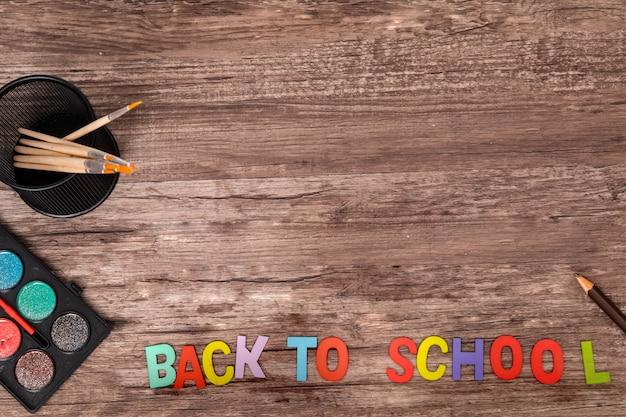 Vue de dessus plat laïc mains de garçon jouent l'alphabet à l'école sur fond en bois avec espace de copie