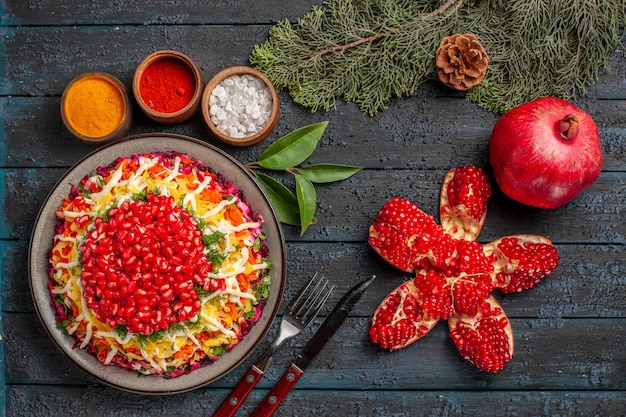 Vue de dessus plat de noël plat de noël avec pommes de terre carottes grenade à côté des bols de grenades pilées de différentes épices branches d'épinette avec cônes sur la table