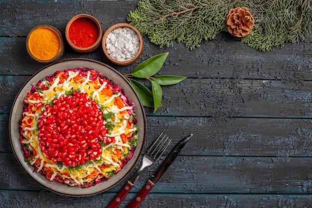 Vue de dessus plat de noël avec pommes de terre carottes grenade à côté des bols de différentes épices branches d'épinette avec cône sur la table