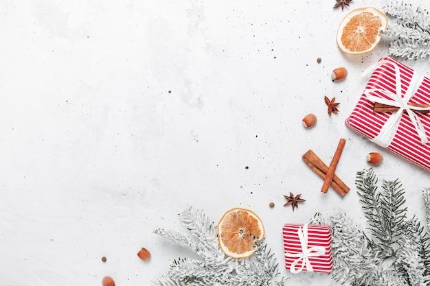 Vue de dessus à plat de noël sur une table de fond en béton gris blanc avec des coffrets cadeaux rouges, des décorations, des bâtons de cannelle, des noisettes, des tranches d'orange séchées, diverses épices, du sapin, de l'anis, de l'anis