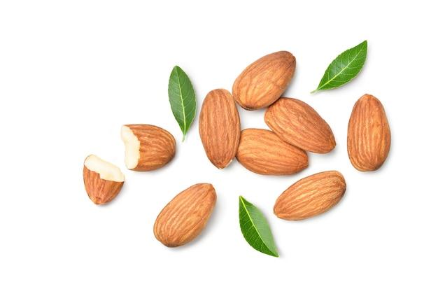 Vue de dessus à plat des noix d'amande avec des feuilles sur fond blanc.