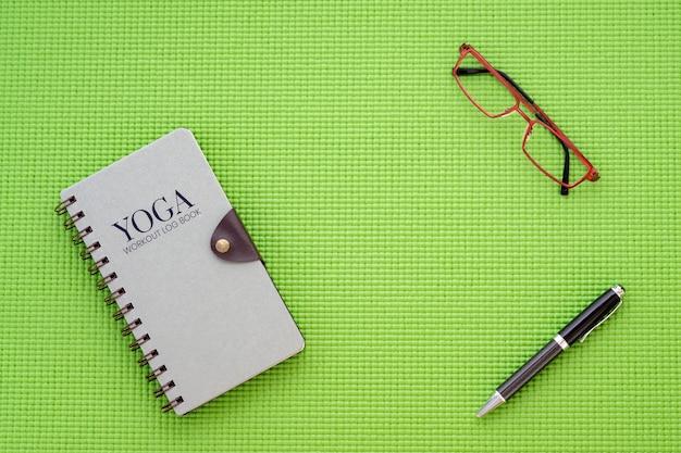 Vue de dessus plat plat du livre de journal d'entraînement de yoga sur le tapis de yoga