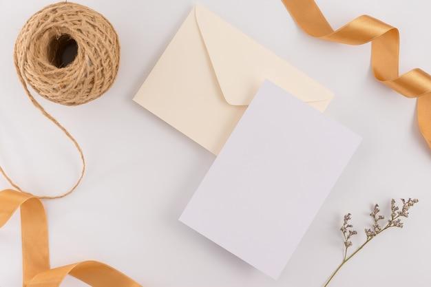 Vue de dessus, plat poser, carte d'invitation de mariage, enveloppes, papiers cartes sur fond blanc.