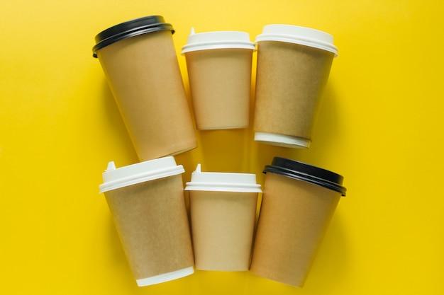 Vue de dessus plat poser gobelets jetables pour boisson à emporter sur jaune