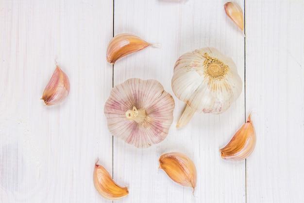 Vue de dessus, plat poser. gousses d'ail et bulbe d'ail sur une table en bois blanche.