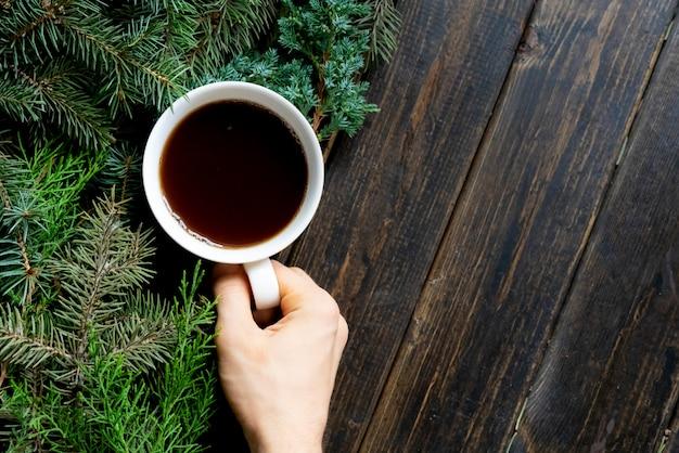 Vue de dessus plat poser tasse de thé près de branches de pin sur une surface en bois.