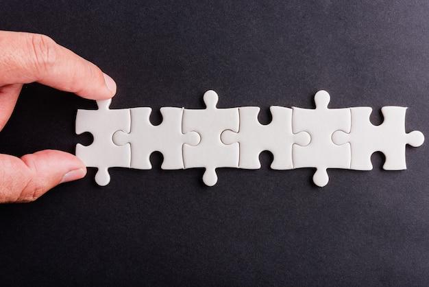 Vue de dessus à plat de la prise en main du dernier jeu de puzzle en papier blanc de six pièces, dernières pièces pour résoudre le problème