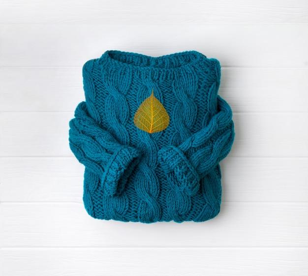 Vue de dessus plat pull en tricot confortable turquoise avec feuille sèche orange sur table en bois blanc
