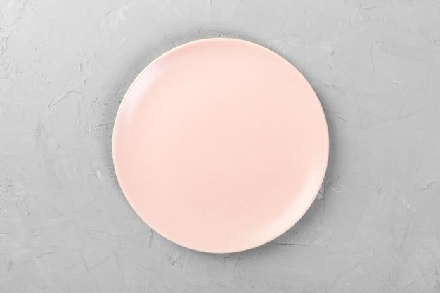 Vue de dessus de plat rond rose vide mat sur l'espace de ciment gris pour vous concevoir