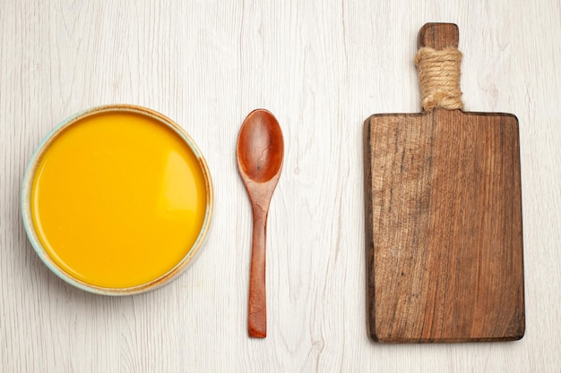 Vue de dessus d'un plat texturé à la crème de soupe à la citrouille savoureuse sur blanc