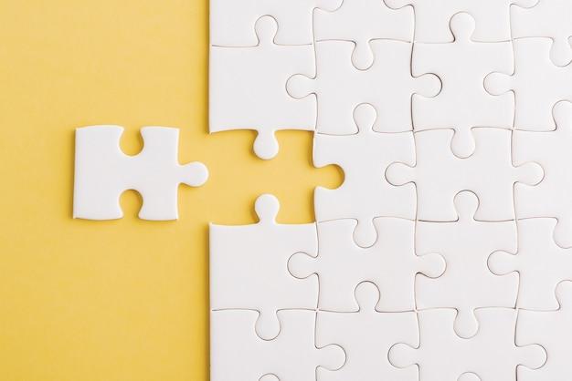 Vue de dessus à plat de la texture du jeu de puzzle blanc uni, dernières pièces pour résoudre et placer