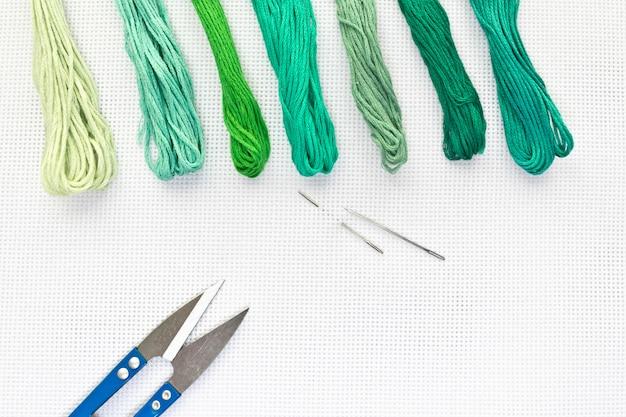 Vue de dessus à plat avec une toile à broder, des aiguilles et des fils de couleurs vertes