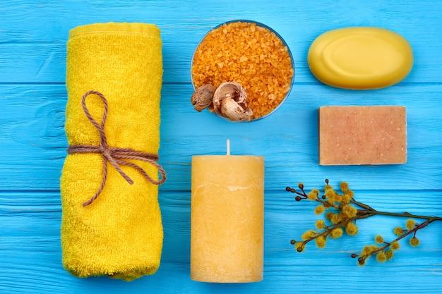 Vue de dessus à plat sur des trucs de spa de salle de bain sur bois bleu. serviette jaune avec sel, bougie, savon et saule.