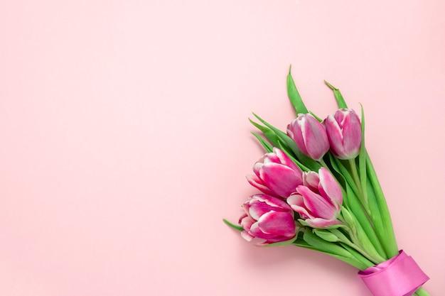 Vue de dessus plat tulipes roses mignonnes avec ruban de soie sur un rose tendre