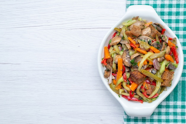 Vue de dessus plat de viande en tranches avec des légumes cuits à l'intérieur de la plaque sur le fond clair repas alimentaire viande de légumes