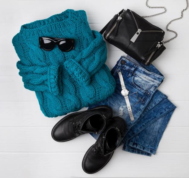 Vue de dessus plate look décontracté féminin avec un pull turquoise chaud, des bottes, un jean, un sac à main, une montre et des lunettes de soleil