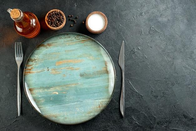 Vue de dessus plateau rond couteau à dîner et fourchette poivre noir et bouteille d'huile de sel sur table noire avec espace libre
