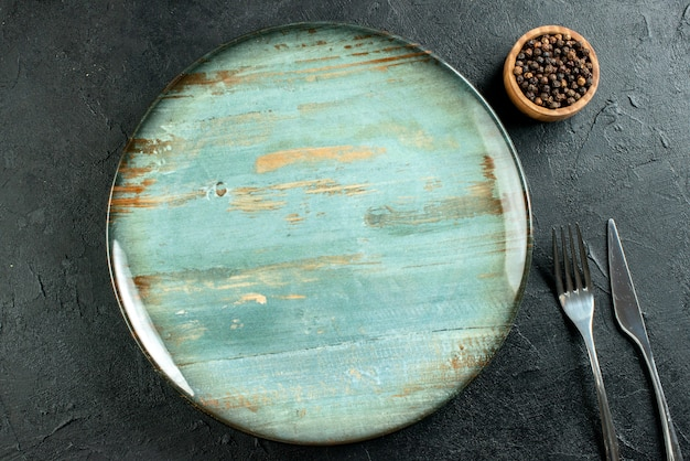 Vue de dessus plateau rond couteau à dîner et fourchette poivre noir dans un bol sur table noire