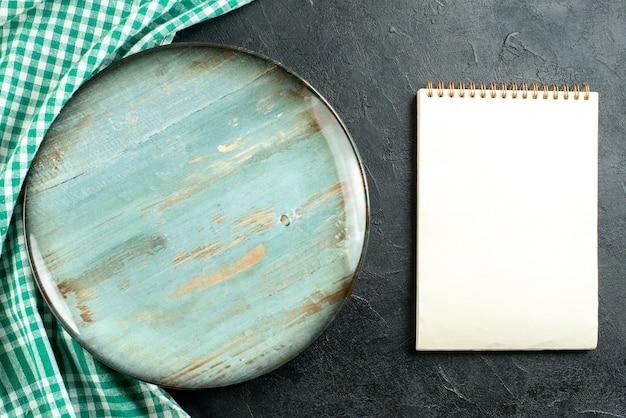 Vue de dessus plateau rond nappe verte et blanche cahier sur table noire