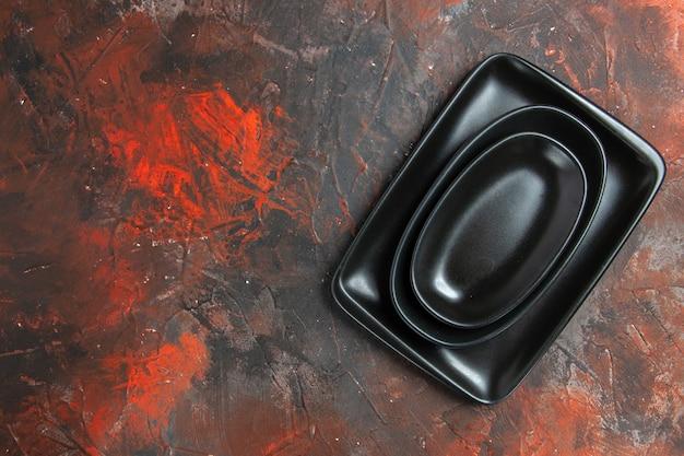 Vue de dessus des plateaux ovales et rectangulaires noirs sur une surface rouge foncé