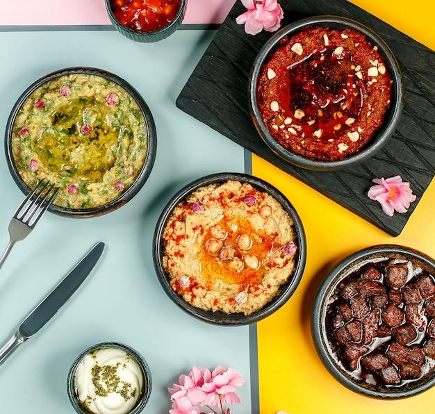 Vue de dessus des plats d'accompagnement bols avec mélange d'aubergine de houmous et mélange de poivrons épicés