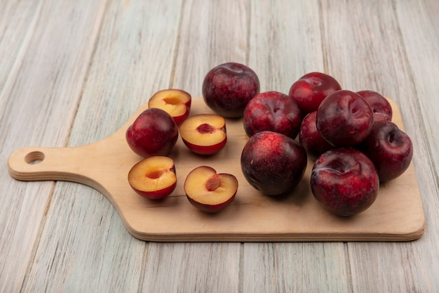 Vue de dessus des pluots frais et juteux isolés sur une planche de cuisine en bois sur un fond en bois gris