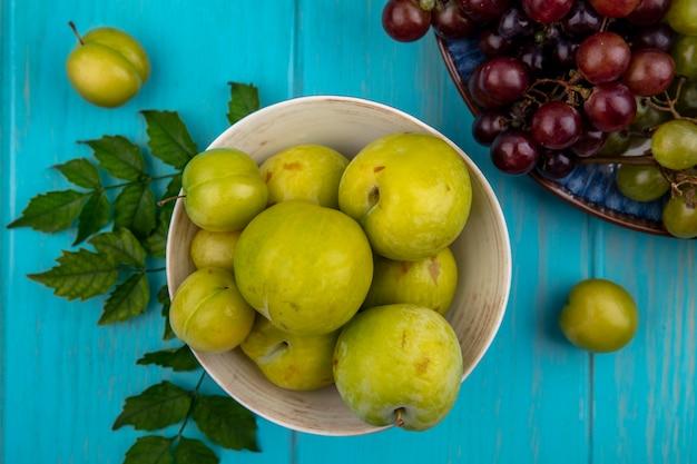 Vue de dessus des pluots verts dans un bol avec assiette de raisins sur fond bleu décoré de feuilles