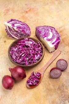 Vue de dessus plusieurs oignons rouges et chou rouge haché dans un bol en bois pour salade de betteraves sur un fond en bois avec place pour copie