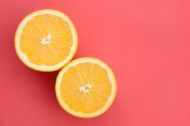 Vue de dessus de plusieurs tranches de fruits orange sur fond clair de couleur rouge. une image de texture d'agrumes saturée