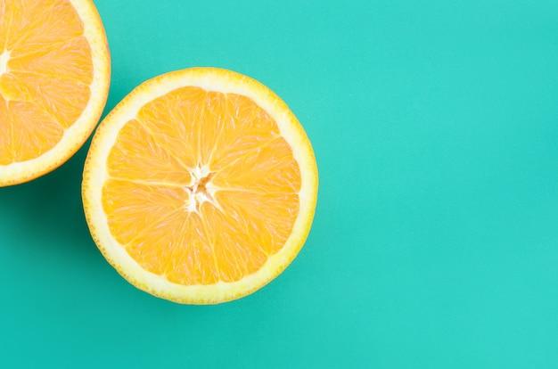 Vue de dessus de plusieurs tranches de fruits orange sur fond clair de couleur vert turquoise. une image de texture d'agrumes saturée