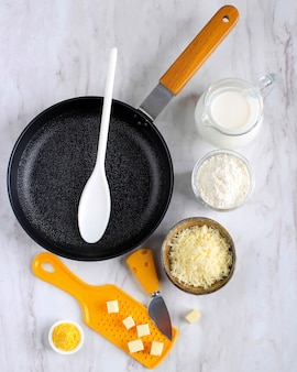 Vue de dessus poêle à frire, fromage, farine, lait, préparation d'ingrédients de sauce béchamel (sauce blanche pour pâtes) sur une table en marbre blanc