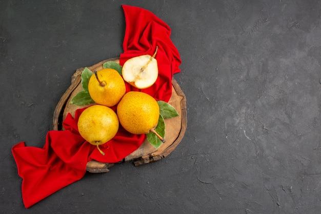 Vue de dessus des poires douces fraîches sur du tissu rouge et du bureau sombre de couleur douce mûre et fraîche