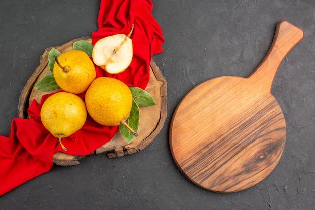 Vue de dessus des poires douces fraîches sur du tissu rouge et du sol sombre de couleur douce mûre et fraîche
