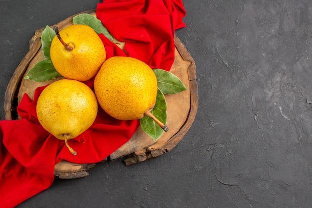 Vue de dessus des poires douces fraîches sur du tissu rouge et de la table sombre de couleur douce mûre et fraîche
