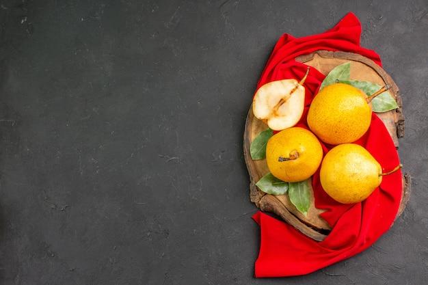 Vue de dessus des poires douces fraîches sur un tissu rouge et une table sombre de couleur fraîche et moelleuse