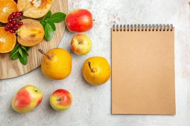 Vue de dessus des poires fraîches avec d'autres fruits sur une table blanche fruits mûrs moelleux frais