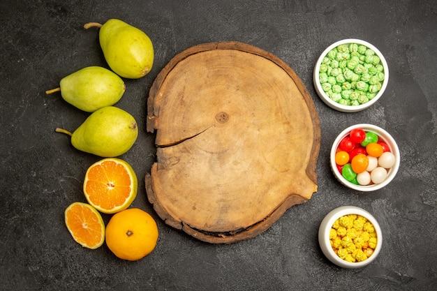 Vue de dessus des poires fraîches aux mandarines sur gris-noir