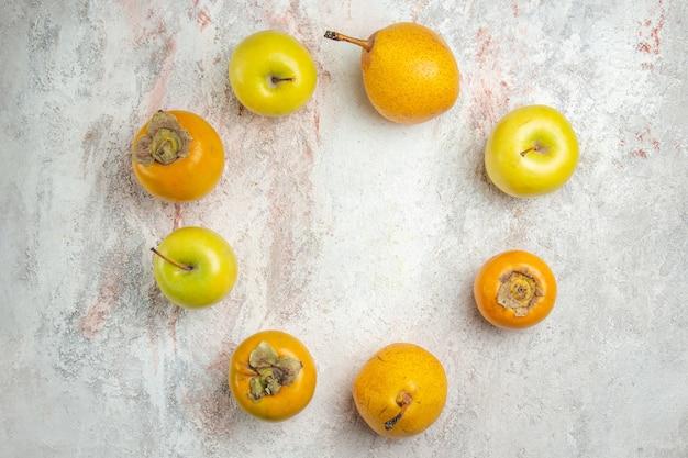 Vue de dessus des poires fraîches avec des kakis et des pommes sur des fruits de table blancs frais moelleux mûrs