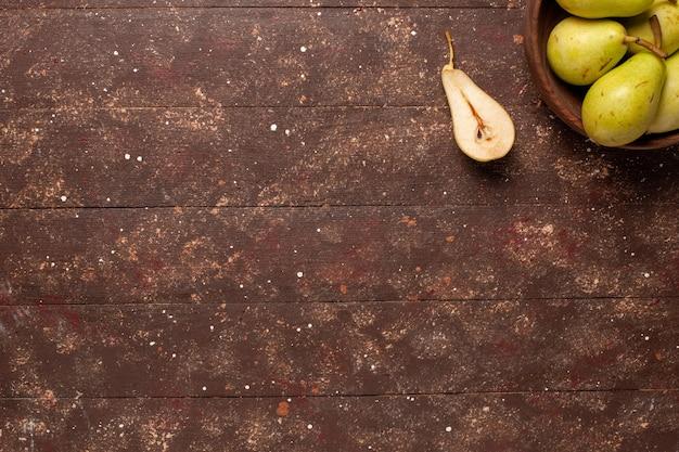 Vue de dessus poires moelleuses fraîches vertes et juteuses sur l'espace brun