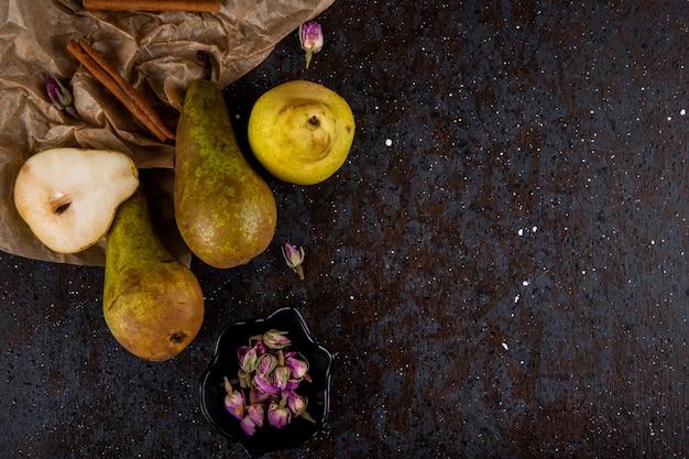 Vue de dessus de poires mûres fraîches avec un morceau de papier kraft bâtons de cannelle et boutons de rose de thé sur fond noir avec copie espace