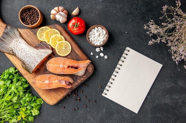 Vue de dessus poisson frais au citron et légumes verts sur fond sombre salade de poisson eau viande océan mer dîner repas de fruits de mer