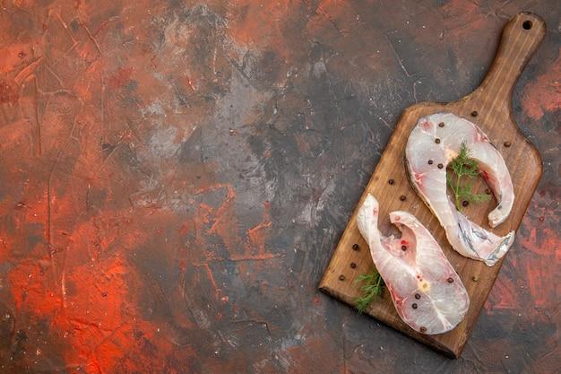 Vue de dessus des poissons crus frais et du poivre sur une planche à découper en bois sur la surface de couleur de mélange
