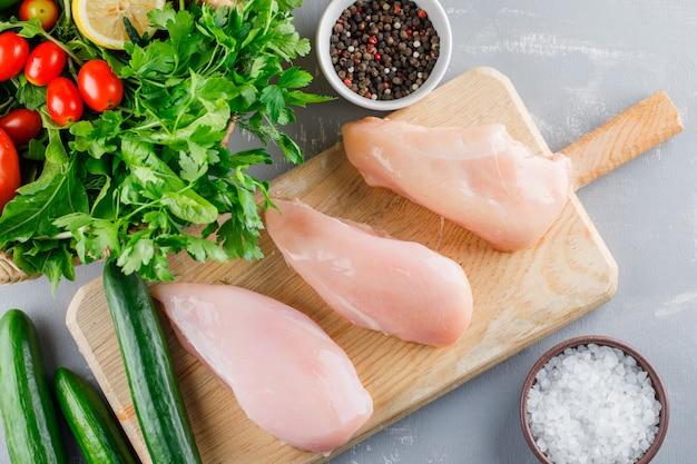 Vue de dessus de poitrine de poulet sur une planche à découper avec concombre, légumes verts, sel, poivre sur la surface grise
