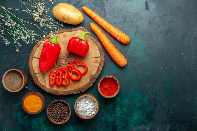 Vue de dessus poivron rouge avec différents assaisonnements sur la nourriture chaude épicée de légumes de surface vert foncé