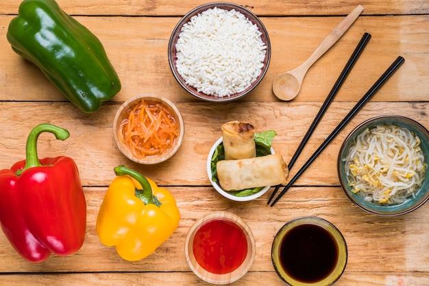 Une vue de dessus des poivrons; carotte; riz; rouleaux de printemps; germer des haricots et des sauces avec des baguettes et une louche sur un bureau en bois
